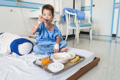 Asian patient boy with saline intravenous (iv) on hospital bed. Stock Photos