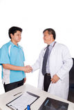 Asian patient thank and shakes hand with medical doctor stock photography