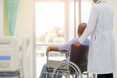 Asian patient in wheelchair sitting in hospital corridor with As stock image