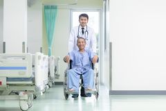 Asian patient in wheelchair sitting in hospital corridor with Asian male doctor, Medical equipment concept stock photos