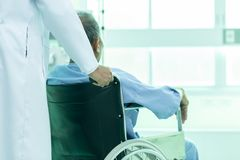 Asian patient in wheelchair sitting in hospital corridor with As royalty free stock photos