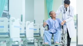 Asian patient in wheelchair sitting in hospital corridor with As. Ian male doctor, Medical equipment concept royalty free stock photography