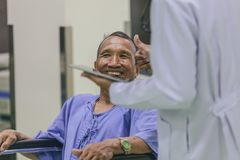 Asian patient in wheelchair sitting in hospital with Asian doctor. royalty free stock photos