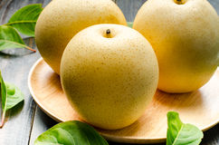 Asian pear. Fresh asian pear (tropical fruit) on wooden background Stock Images