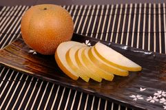 Asian pear on plate. Asian pear whole and sliced on oriental plate Royalty Free Stock Photos
