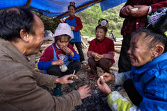 Asian peasants, farmers, villagers, sit around fire,  at rural c Royalty Free Stock Image