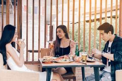 Asian people cheering beer at restaurant happy hour and laughing.  royalty free stock photos