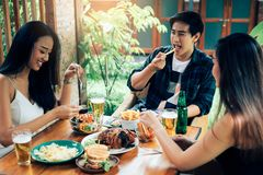 Asian people cheering beer at restaurant happy hour and laughing.  stock image