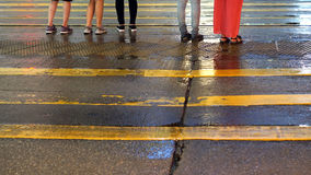Asian people cross wet street with neon light reflection Royalty Free Stock Photo