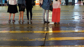 Asian people cross wet street with neon light reflection Stock Photos