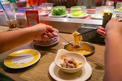 Free Asian People Eating Enoki Mushroom Hotpot At Conveyor Belt Restaurant Royalty Free Stock Photos - 212118708