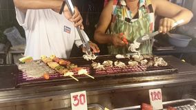Asian people grill fish in street food in Thailand stock video footage