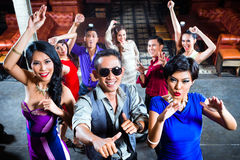 Asian people partying on dance floor in nightclub. Asian party people men and women partying on the dance floor in fancy night club royalty free stock image