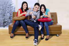 Asian people playing console game. Portrait of young people playing games in the living room with holding joystick and sitting on the brown sofa Stock Images