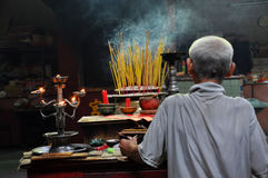 Asian people praying and burning incense sticks in a pagoda Royalty Free Stock Photos