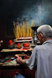 Asian people praying and burning incense sticks in a pagoda Royalty Free Stock Image