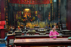 Asian people praying and burning incense sticks in a pagoda Stock Image