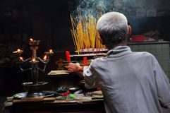 Asian people praying and burning incense sticks in a pagoda Stock Photos