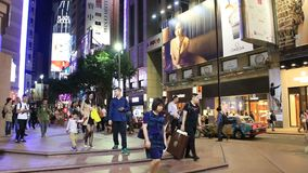 Pedestrians crossing shopping street at night. Asian people rushing through a very busy intersection in the shopping district at night. Neon lights of shopping stock video footage
