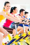 Asian people spinning bike training at fitness gym. Chinese Asian sport group of men and women in fitness club or gym exercising on spinning bikes royalty free stock photography