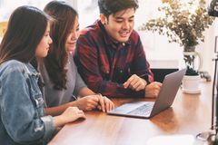 Asian people using and looking at the same laptop computer during a meeting royalty free stock images