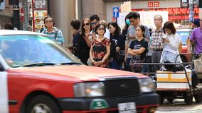Asian people waiting at crosswalk on busy street stock video