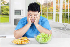 Asian person confused to choose food. Overweight Asian person sitting in the kitchen and looks confused to choose hamburger or salad royalty free stock photos