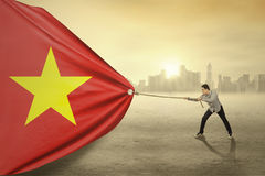 Asian person dragging flag of Vietnam Royalty Free Stock Photography