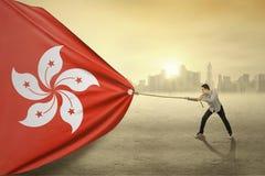 Asian person pulling flag of Hongkong Stock Images