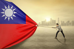 Asian person pulling flag of Taiwan Stock Photos
