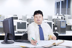 Asian person working while eating in office Royalty Free Stock Photos