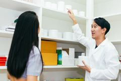 Asian pharmacist doctor in professional gown explaining and giving advice with female client in drugstore shop. stock images