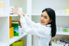 Asian pharmacist doctor in white gown checking medical health stock products and working in drugstore in shop. stock photography