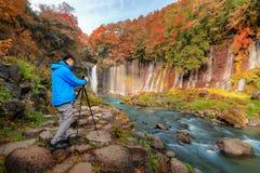 Asian photographer taking landscape photos of waterfall. Fall foliage in autumn season near Fujikawaguchiko, Yamanashi. Trees in stock image