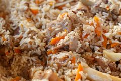Asian pilaf consisting of brown rice, pieces of stew lamb, carrots, garlic and other spices. Close-up stock images