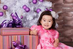 Asian pin up little cute girl wearing pink casual dress posing close to new year christmas white tree with violet purple balls toy Royalty Free Stock Images