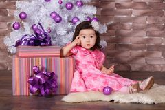 Asian pin up little cute girl wearing pink casual dress posing close to new year christmas white tree with violet purple balls toy Royalty Free Stock Photo