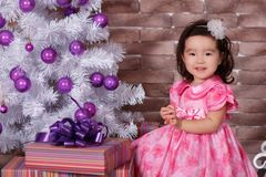Asian pin up little cute girl wearing pink casual dress posing close to new year christmas white tree with violet purple balls toy Stock Photo