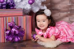 Asian pin up little cute girl wearing pink casual dress posing close to new year christmas white tree with violet purple balls toy Stock Image