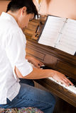 Asian playing piano Stock Photo