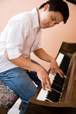 Asian playing piano Stock Photography