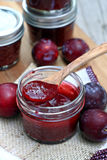 Asian Plum Sauce. Jar of plum sauce with wooden spoon royalty free stock photo