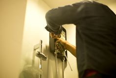 Asian plumber fixing water heater in the bathroom with hand hold. Ing driver, Shot through bathroom glasses stock photos