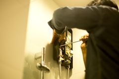Asian plumber fixing water heater in the bathroom using dr. Iver, Shot through bathroom glasses royalty free stock photo