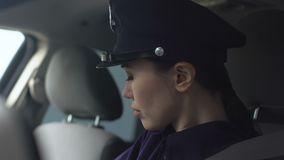 Asian policewoman getting into squad vehicle and preparing to drive, occupation