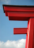 Asian port. Detail of a wooden, red painted, oriental port against a blue sky stock image