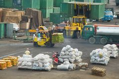 Asian port dockers loading cargo. (bananas, flour bags) and freight from the quay into ship with containers in the background in Cebu City port (Southern Royalty Free Stock Images