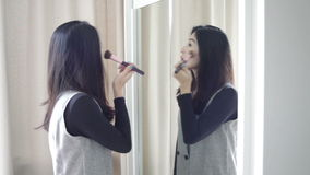 Asian portrait beautiful woman making or applying make-up with brush on eyebrow and looking in the mirror in full HD stock video