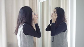 Asian portrait beautiful woman making or applying make-up with brush on eyebrow and looking in the mirror in full HD stock video footage