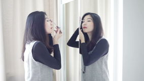 Asian portrait beautiful woman making or applying make-up with brush on eyebrow and looking in the mirror in full HD stock footage